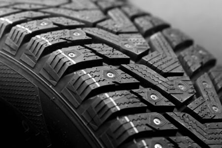 Close-up side view of a large studded tire. Automotive industry concept. The concept of seasonal tire updates. Concept of trucks and cars wheels Stock Photo - 136109293