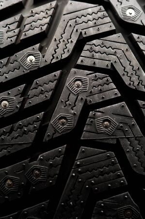 Close-up studded car tire stands on a black background. Automotive industry concept. The concept of sports equipment in the gym. Place for text Stock Photo - 136110515
