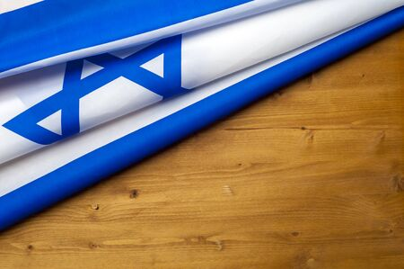 Top view of flag of Israel lies on wooden table