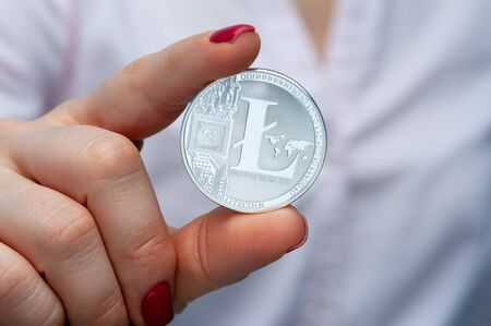 Hands of a young unidentified woman holding a litecoin coin in their hands. Risky currency concept. The concept of mining and unstable earnings Фото со стока