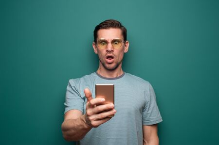 Portrait of a shocked young man with smartphone 写真素材