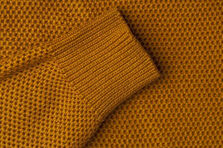 Close-up of an orange knitted fabric from a sweater or other woolen product. The concept of warm cozy products. Handmade product. Place for text 写真素材