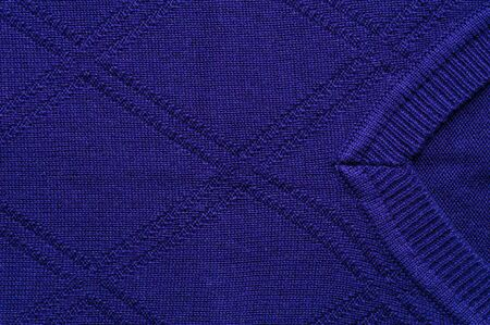 Close-up fragment of the neck knitted blue sweatshirt. Concept of warm autumn and spring things. Quality Woolen Clothing Concept. Sewing concert