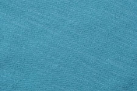 Close-up fragment of light blue cotton linen fabric. Concept of quality fabric for sewing clothes. Advertising space. Place for text