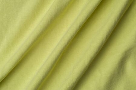Close-up fragment of a beautiful yellow cotton fabric. Concept of high-quality raw materials for tailoring casual clothes. Advertising space 写真素材