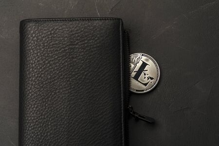 Close-up of a silver bitcoin coin lies on a black wallet. The concept of mining and risky business. Finance and currency concept. Advertising space