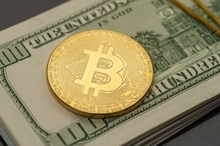 Close-up of a silver bitcoin coin lies on a hill of hundred-dollar bills tightened by a clerical gum. Concept of modern money electronic and paper money 写真素材