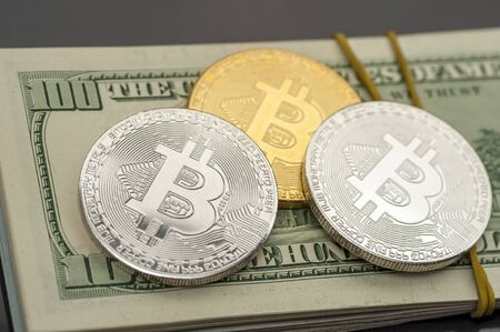 Close-up of Bitcoin coins lie on piles of hundred-dollar bills pulled out of clerical gum and a euro bill. Concept of current money and and stable currencies