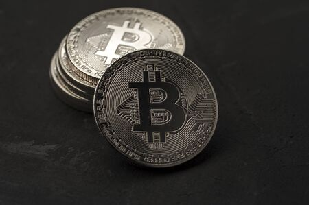 Close-up of a stack of silver Bitcoin coins lies on a black background. The concept of modern and unstable currencies. Advertising space