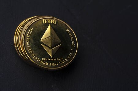 Close-up of a gold Bitcoin coin lies on a black background. The concept of modern currencies and mining. Place for advertising