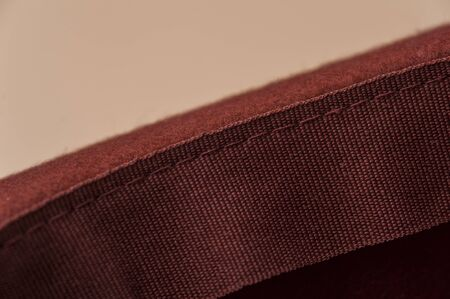 Close-up closeup of a field of burgundy hat with ribbon. Concept of hats and womens clothing. Autumn and Spring Clothing Concept. Advertising concept