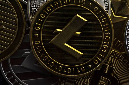 Close-up of a gold coin of bitcoin lies on the silver and gold coins of bitcoins. E-money mining concept. Modern unstable currency.
