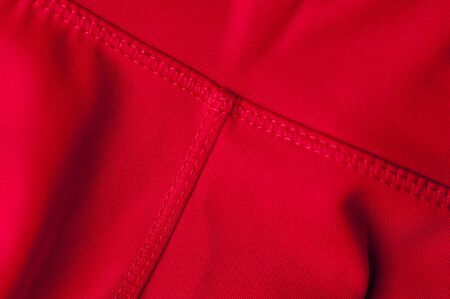 Close-up fragment of crumpled red polyester fabric. Concept of high-quality raw materials for clothing. Advertising space. Concept of sewing womens clothing