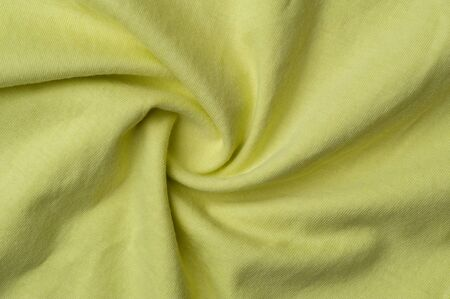 Close-up fragment of crumpled beautiful yellow cotton fabric. Concept of high-quality raw materials for tailoring casual clothes. Advertising space 写真素材