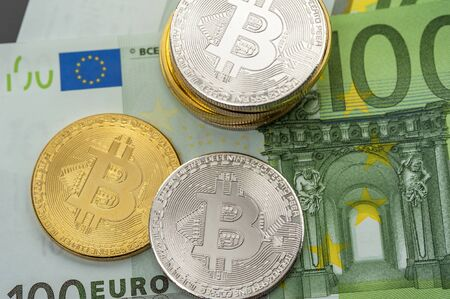 Close-up silver and gold bitcoin coins lie on one hundred euro banknotes of modern money. Concept of electronic and real money
