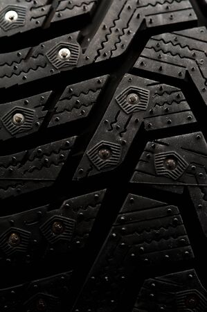 Close-up studded car tire stands on a black background. Automotive industry concept. The concept of sports equipment in the gym. Place for text