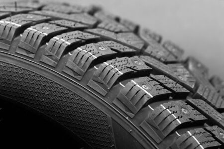Close-up side view of a large studded tire. Automotive industry concept. The concept of seasonal tire updates. Concept of trucks and cars wheels
