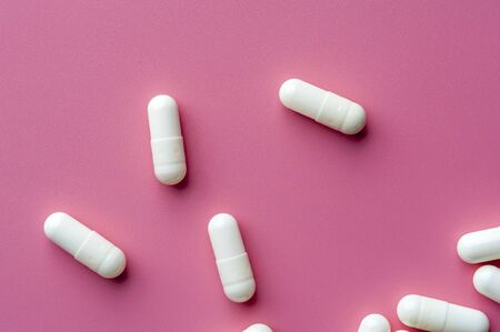 Close-up of white pills lie on a pink surface