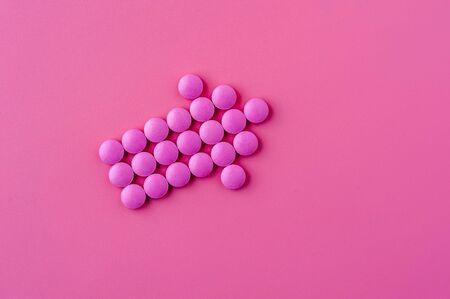 Close-up of pink pills lie on a pink surface