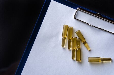 Close-up glass ampoules with medicine on empty sheet 스톡 콘텐츠