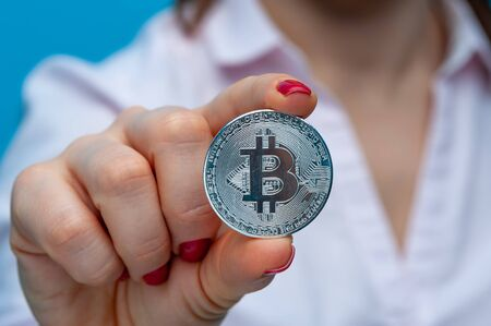 Young unidentified woman holding a bitcoin coin Stock Photo