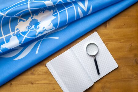 Close-up of the UN blue flag with the image of the countries participating in a magnifier and a notebook lying on a wooden table. The concept of peace treaties and strategic decisions