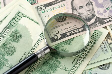 Magnifying glass lies on scattered dollar Banco de Imagens