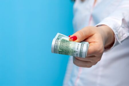Woman holds rolled paper banknotes