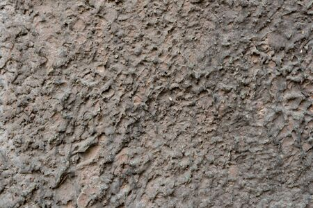 Close-up - gray-brown stone wall in the old facade of the house - background image