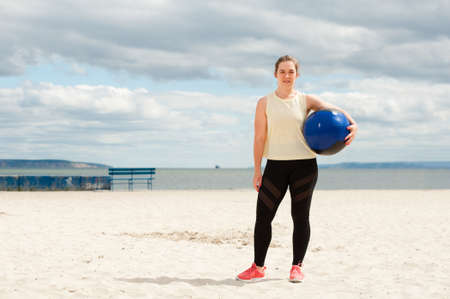 Athletic woman with medicine ball at outdoor fitness gym.