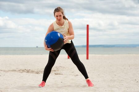 Fit healthy woman wearing sportswear training legs and glutes with heavy ball.