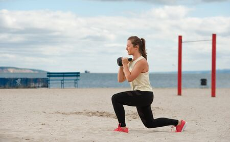 Fit healthy woman wearing sportswear training legs and glutes with kettlebell