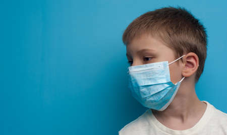 Side portrait of child boy wearing a medical mask. Flu epidemic, dust allergy, protection against virus.