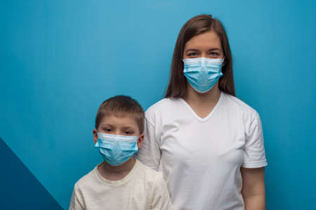 Stay at home. Caucasian mother and son wearing protective medical mask. Flu epidemic, dust allergy, protection against virus.