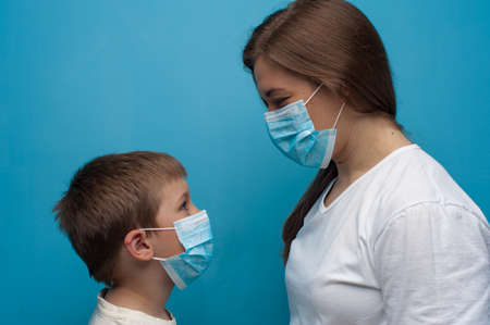 Protection against virus. Stay at home. Caucasian mother and son wearing protective medical mask. Flu epidemic, dust allergy.