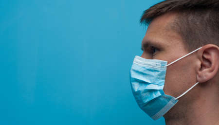 Side portrait of young woman wearing a medical mask. Flu epidemic, dust allergy, protection against virus.