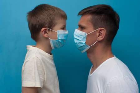 Protection against virus. Stay at home. Caucasian father and son wearing protective medical mask. Flu epidemic, dust allergy. 版權商用圖片