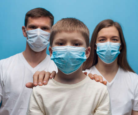 Stay at home. Parents and child son wearing protective medical mask. Flu epidemic, dust allergy, protection against virus.