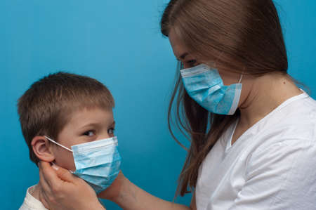 Portrait of caucasian mother and son wearing protective medical mask. Flu epidemic, dust allergy, protection against virus.