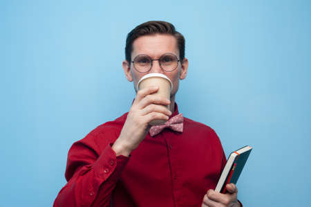 Portrait of a smiling handsome young man in glasses and a red shirt holding a glass of coffee with him on a blue background. Tea and coffee drinks concept