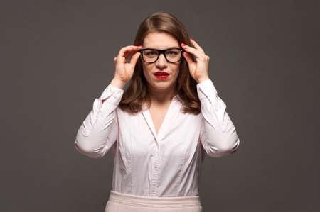 Young woman with stylish eyeglasses and red lips posing over grey background.