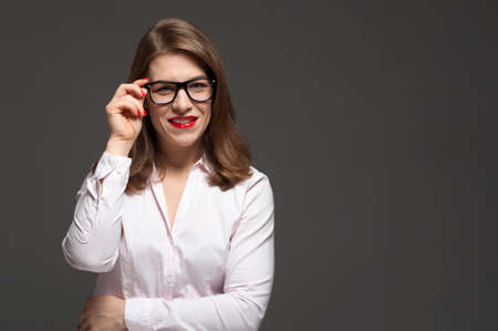 Happy smiling young woman wearing eyeglasses posing on grey background. Free space for design. Imagens