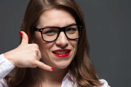 Close-up portrait of young woman with eyeglasses and red lips posing over grey background. 版權商用圖片