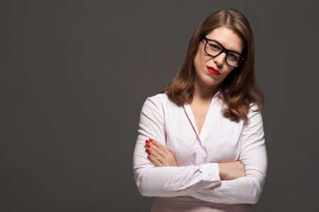 Attractive young woman wearing eyeglasses posing on grey background. Free space for design.