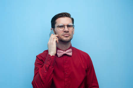 Portrait of a handsome young man in a red shirt and glasses with a smartphone posing on a blue background.