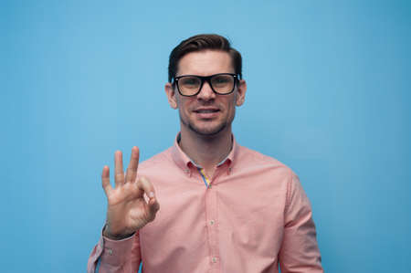 Portrait of a happy young man in glasses and a pink shirt joyfully showing ok on a blue background. Concept of successful lucky young man