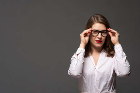 Portrait of young attractive business woman wearing eyeglasses and formal shirt. Place for design and advertising. Imagens