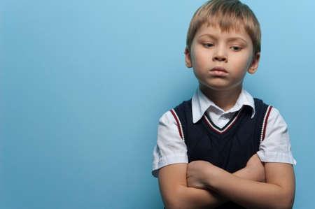 Little boy an elementary school student posing on blue background.