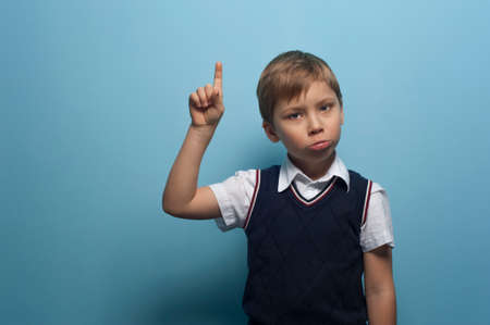 Funny Little boy an elementary school student pointing his finger posing on blue background.