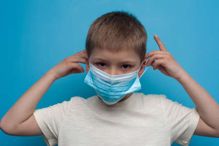 Portrait of child wearing an anti virus protection mask to prevent corona virus. Фото со стока